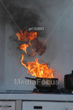 Flames From Burning Oil On A Kitchen Stove Stock Photo