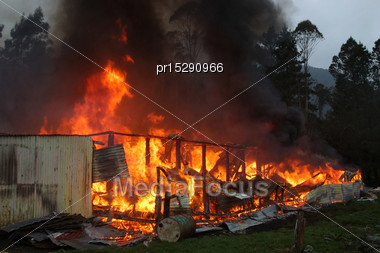 Flames And Smoke Rise From Burning Building Stock Photo