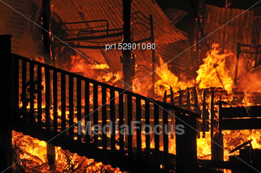 Flames And Smoke Rise From Burning House Stock Photo