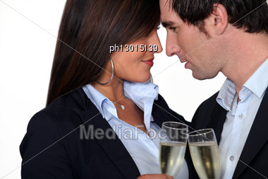 Flirtatious Business Couple Drinking Champagne Stock Photo