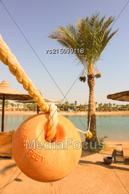 Floats On Sun Beach Background. Buoys Dry Out Between Palm Trees Stock Photo