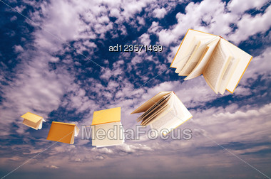 Flock Of Books Flying On Blue Sky Background Stock Photo