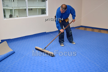 Floorlayer Carefully Uses A Wide Broom To Smooth Out The Wrinkles In His Newly Laid Carpet Stock Photo