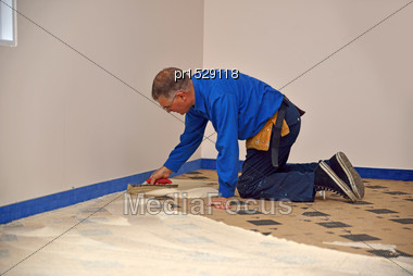 Floorlayer Spreading Adhesive On The Underlay For A Carpet Laying Job Stock Photo