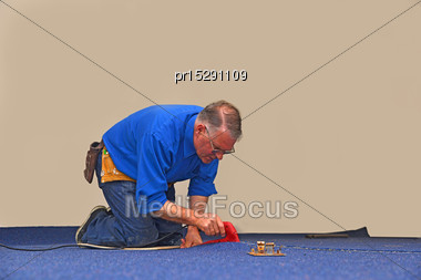 Floorlayer Uses A Hot Iron To Seal The Glue Strip In A Join A New Carpet Stock Photo