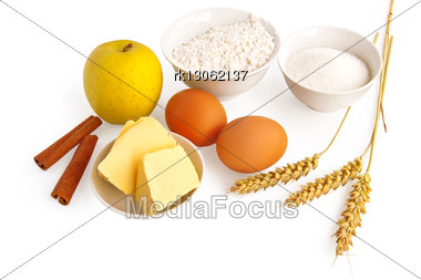 Flour, Sugar And Butter In A Cup, Apple, Two Sticks Of Cinnamon, Two Eggs And Wheat Stalks Isolated Stock Photo