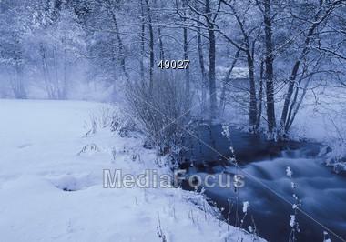 Flowing Stream In Frozen Winter Landscape Stock Photo