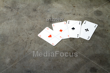 Four Aces On A Cement Floor Stock Photo