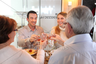 Four Adults Making A Toast At Dinner Stock Photo