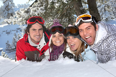 Four Friends Laying In The Snow Stock Photo