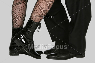 Four Legs In Black Footwear On The Grey Background Stock Photo