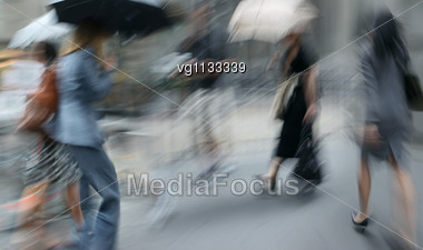 Four Women Rushing On The Rainy Street In Intentional Motion Blur And Tint Stock Photo