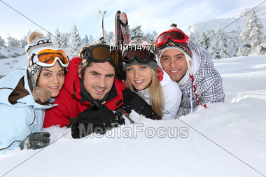 Four Young Adults Laying In The Snow Stock Photo