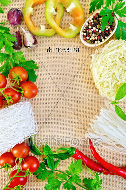 Frame Made Of Rice Noodles, Tomatoes, Sweet And Hot Peppers, Peas Various Pepper In Wooden Spoon, Parsley, Basil And Garlic On Sacking Stock Photo