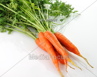 Fresh Carrots With Green Leaves On White Background Stock Photo