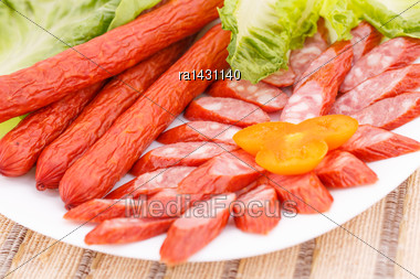 Fresh Sausages And Green Salad Leaves In Plate On Bamboo Mat Background Stock Photo