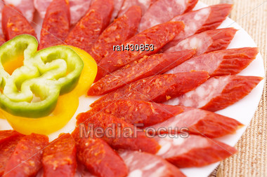 Fresh Sausages And Peppers In Plate On Bamboo Mat Background Stock Photo