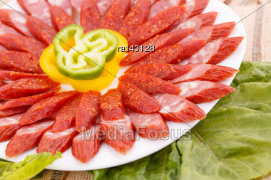 Fresh Sausages, Peppers In Plate And Green Salad Leaves On Bamboo Mat Background Stock Photo