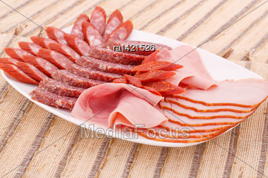 Fresh Sausages In Plate On Bamboo Mat Background Stock Photo
