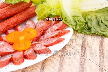 Fresh Sausages In Plate And Green Salad Leaves On Bamboo Mat Background Stock Photo