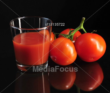 Fresh Tomatoes And Tomato Juice On Black Background Stock Photo