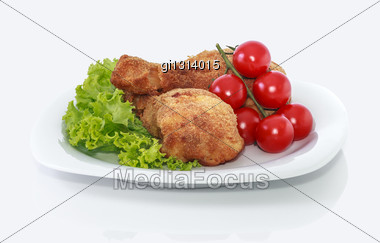 Fried Chicken Pieces On A Plate With Lettuce And Tomatoes. Taken On A Sheet Of White Plastic. Is Not An Isolate Stock Photo