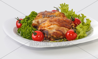 Fried Chicken Pieces On A Plate With Tomatoes, Lettuce And Parsley. Taken On A Sheet Of White Plastic. Is Not An Isolate Stock Photo