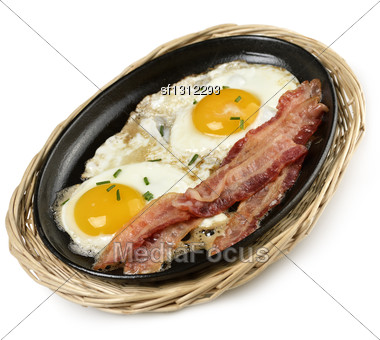 Fried Eggs And Bacon In A Skillet Stock Photo