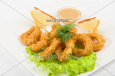 Fried Squid With Salad Leaves, Sauce, Green And Lemon Stock Photo