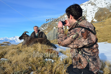 Friend Photographs A Succesful Hunter With The Introduced Himalayan Goat, Or Tahr, (Hemitragus Jemlahicus), South Westland, South Island, New Zealand, With Mount Cook In The Background Stock Photo