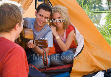 Friends Camping & Playing Guitar Stock Photo