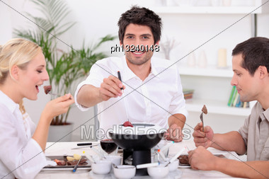Friends Enjoying Chocolate Fondue Stock Photo