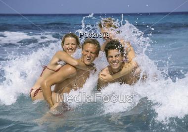 Friends Having Fun In Ocean Waves Stock Photo