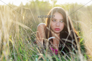 Frightened Young Brunette Hiding In The Dry Grass Stock Photo
