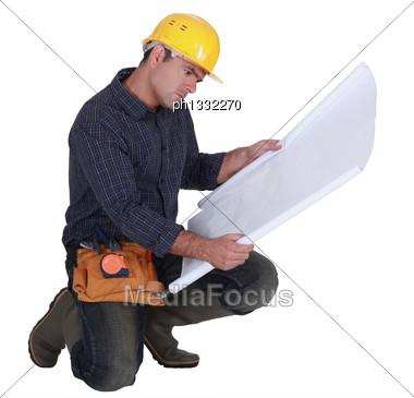 Frowning Tradesman Examining A Blueprint Stock Photo