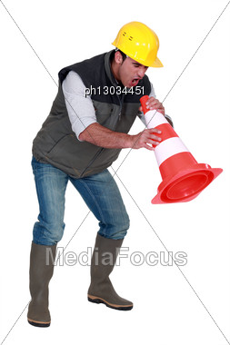 Frustrated Builder Shouting Into Traffic Cone Stock Photo