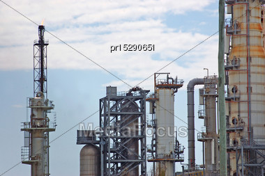 Gas Burning Off On Refractory Towers At Oil Refinery Stock Photo