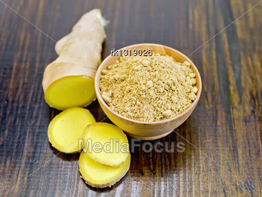 Ginger Powder In A Wooden Bowl And Sliced Ginger Root On A Dark Wooden Board Stock Photo