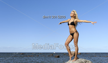 Girl In Bikini Posing On A Rock In A Deep Blue Sea, Arms Outstretched To The Sides Stock Photo