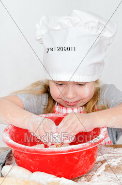 Girl In Chef's Hat The Breaks The Egg In A Bowl Stock Photo