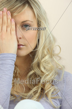 Girl Hiding One Eye Behind Her Hand Stock Photo