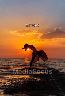Girl Jumping On A Background Of Sea Sunset Stock Photo