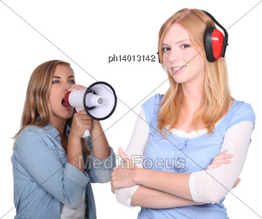 Girl Shouting In Loudspeaker At Female Workmate Stock Photo
