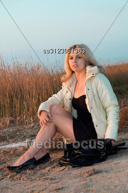 Girl Sitting On The Beach In The Light Of Setting Sun Stock Photo