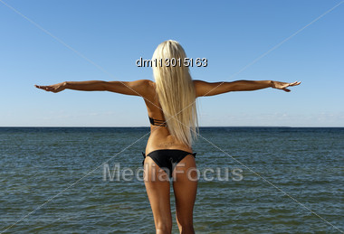 Girl In A Swimsuit Turned Her Back And Looks At The Blue Sea Stock Photo