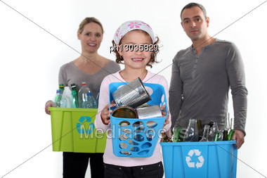 Girl Taking Out Recycling Trash With Parents In Background Stock Photo