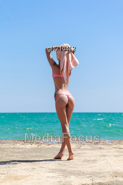 Girl With A Towel On Her Head Looking Into The Distance, Against The Blue Sky And The Sea Stock Photo