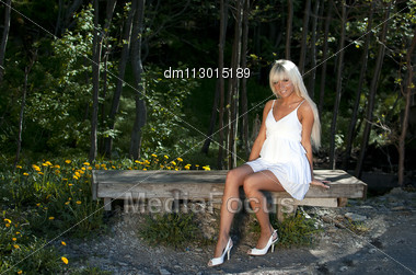 Girl In White Dress Sitting On A Bench In The Woods Stock Photo