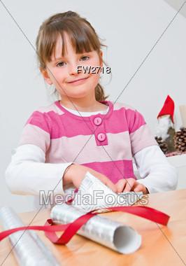 Girl Wrapping Christmas Gift Stock Photo