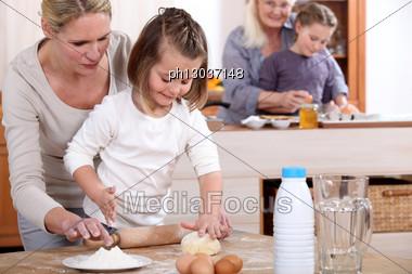 Girls Baking With Mum And Grandma Stock Photo